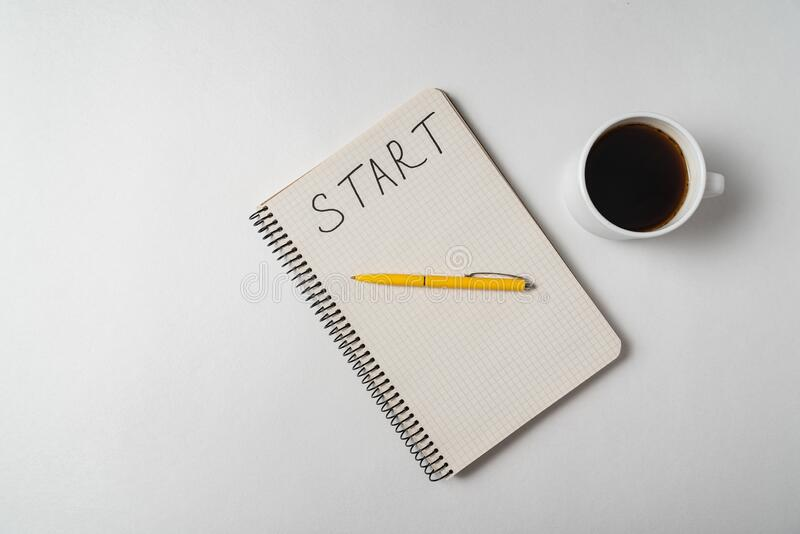 Word START written on notebook over white background. Top view of copybook and coffee royalty free stock images