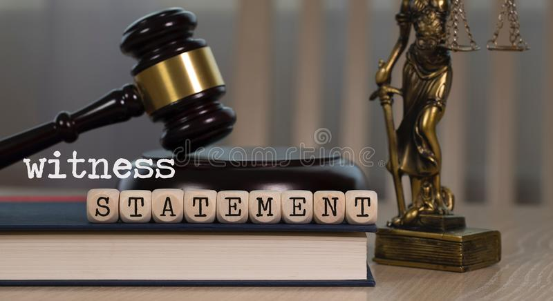Word STATEMENT composed of wooden dices. Wooden gavel and statue of Themis in the background. Closeup, ancient, greek, titaness, book, chair, concept, court stock photography