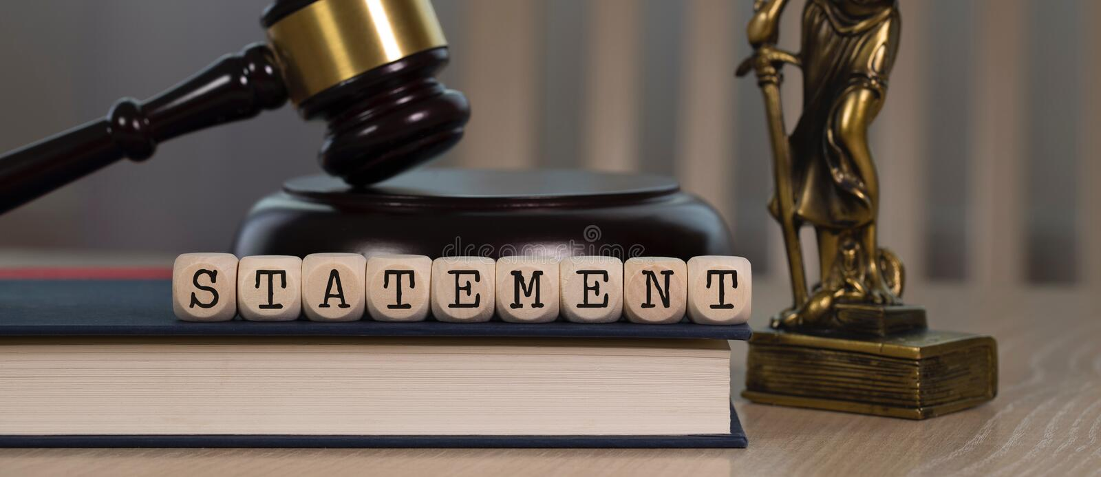 Word STATEMENT composed of wooden dices. Wooden gavel and statue of Themis in the background. Closeup, ancient, greek, titaness, book, chair, concept, court royalty free stock photos