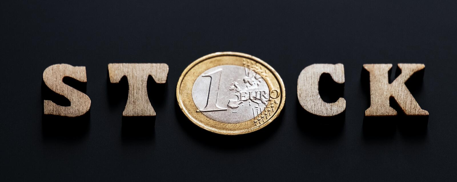 The word STOCK of wooden letters with a coin of one euro instead of the letter O. Black textural background. Shallow depth of stock photography