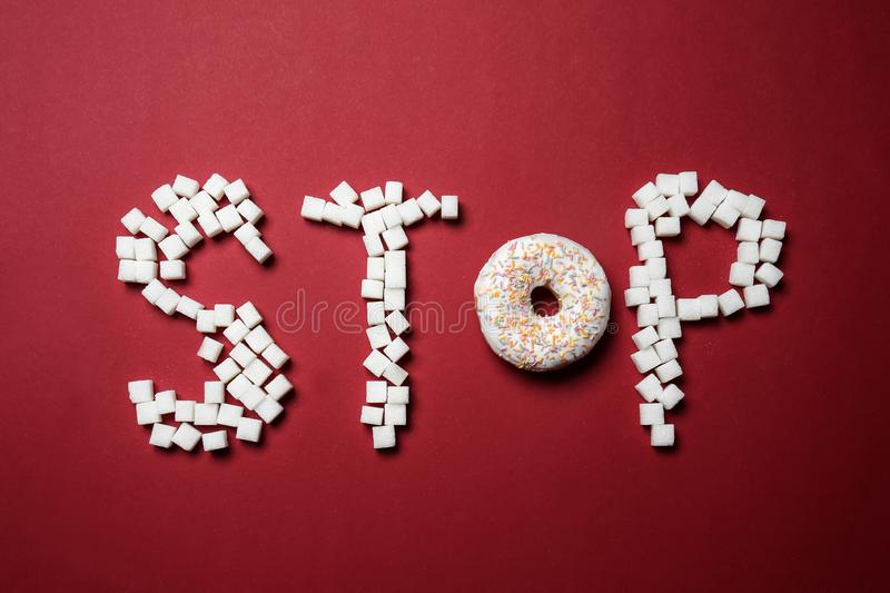 Word STOP made with sugar and doughnut on color background. Concept of addiction royalty free stock images