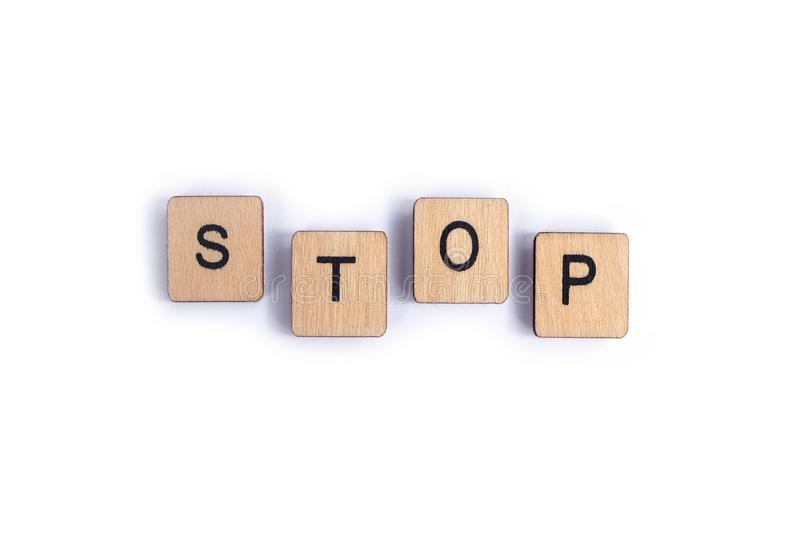 The word STOP. Spelt with wooden letter tiles stock photo