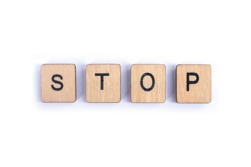 The word STOP. Spelt with wooden letter tiles royalty free stock photo