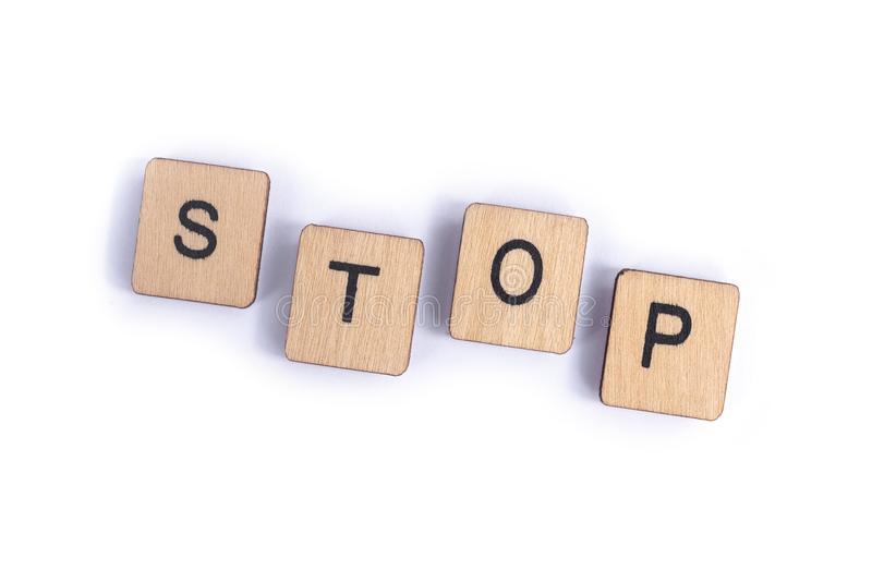 The word STOP. Spelt with wooden letter tiles stock image
