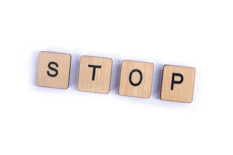The word STOP. Spelt with wooden letter tiles royalty free stock photos