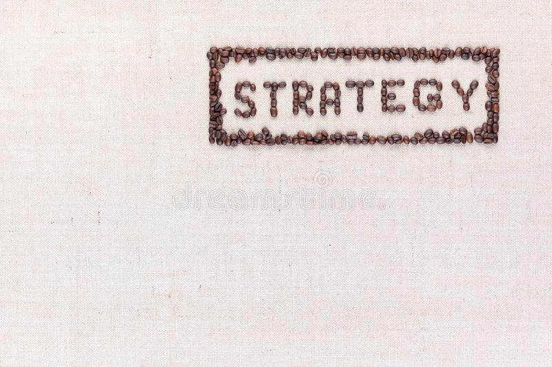 The word Strategy inside a rectangle all made using coffee beans shot from above, aligned to the top right stock image