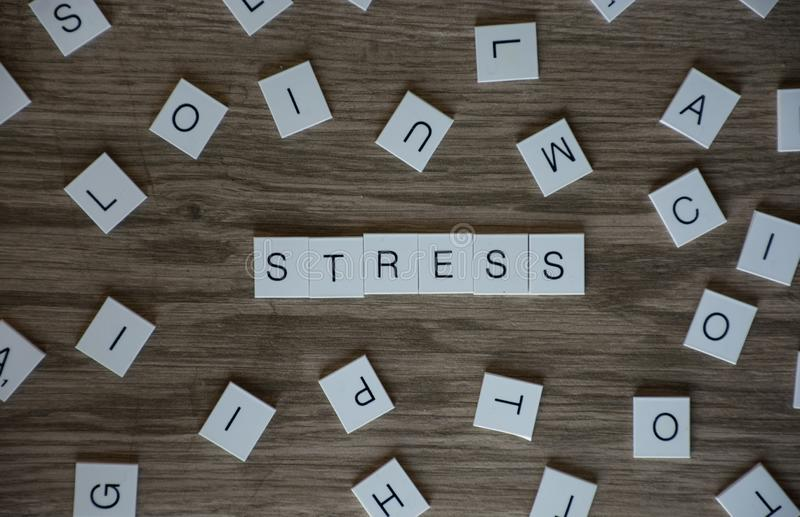Word stress in uppercase letters with single letters all around it. On the floor stock photo