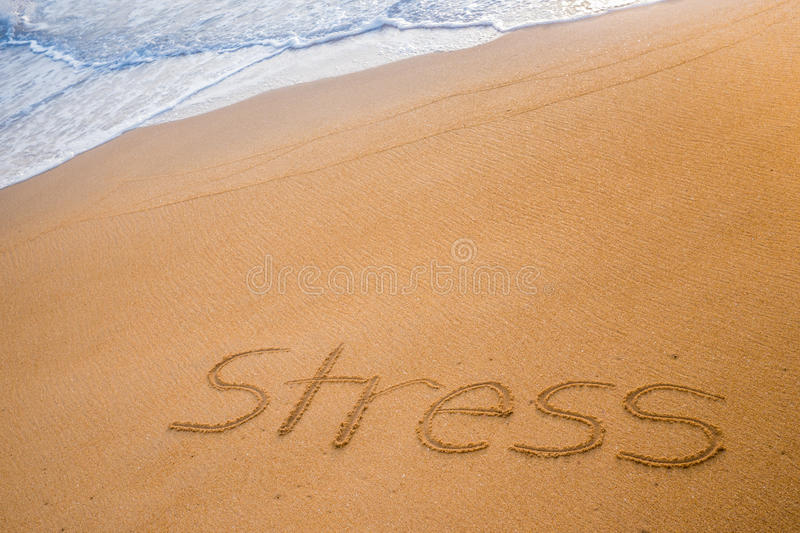 The word STRESS written in the sand royalty free stock photo