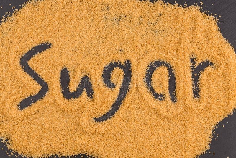 Word suiker in bruine gekorrelde suiker wordt geschreven die royalty-vrije stock foto's