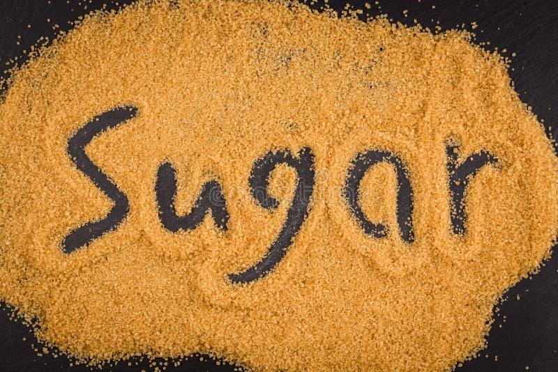 Word suiker in bruine gekorrelde suiker wordt geschreven die royalty-vrije stock afbeelding