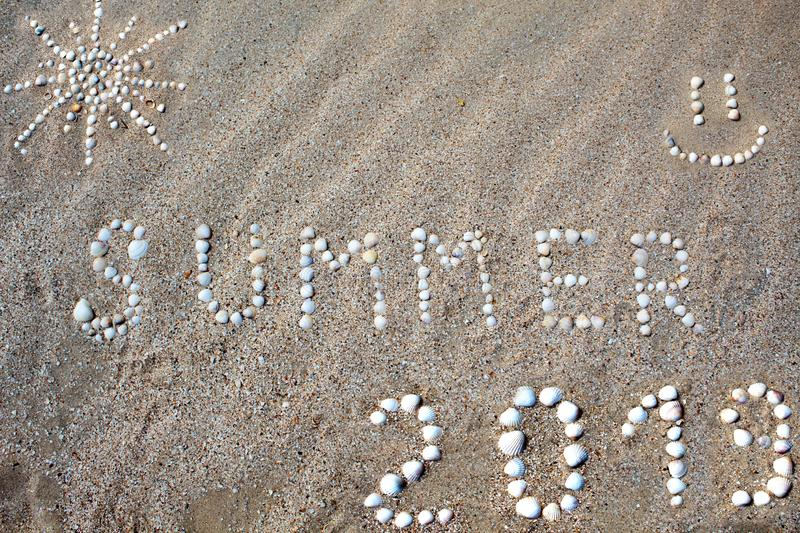 The word summer, the figure of the sun and the smile, the figure 2019 are laid out on the sand with shells. stock images
