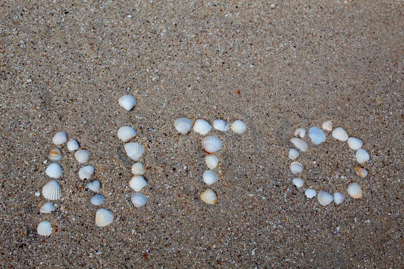 The word summer, laid out on the sand with shells, in the Ukrainian language. royalty free stock photo