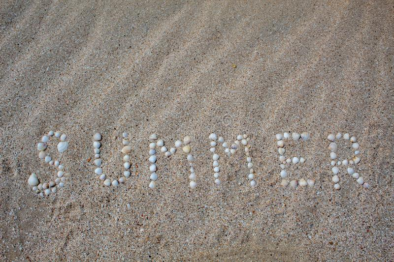 The word summer is laid out on the sand with shells. royalty free stock photography