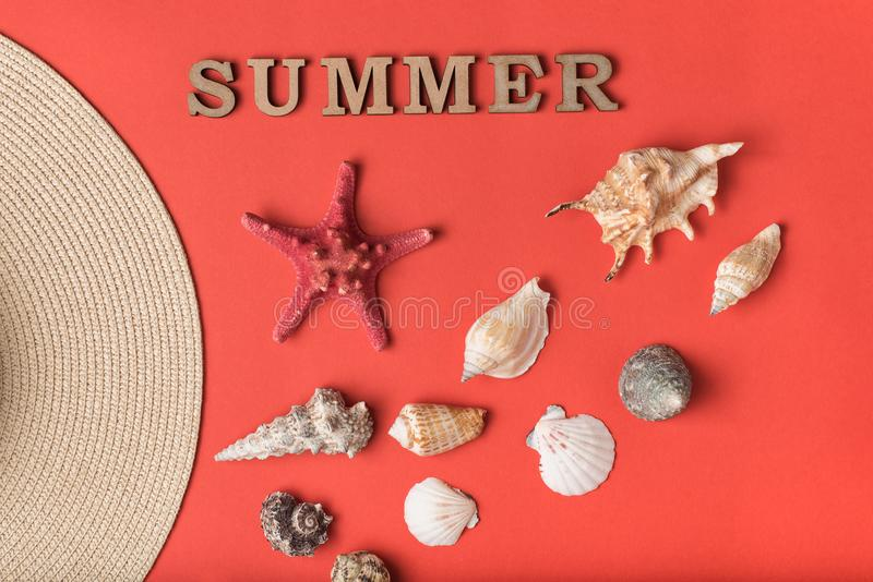 Word Summer from wooden letters. Seashells, part of a hat and a live coral background. Flat lay. Marine concept.  stock images