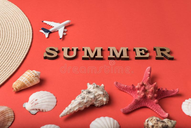 Word Summer from wooden letters. Seashells, small plane and part of a hat. Live coral background. Flat lay. Marine concept.  stock photo
