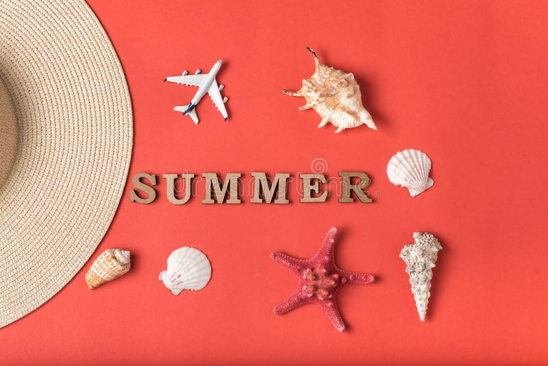 Word Summer from wooden letters. Seashells, small plane and part of a hat. Live coral background. Flat lay. Marine concept.  stock photography