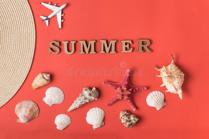 Word Summer from wooden letters. Seashells, small plane and part of a hat. Live coral background. Flat lay. Marine concept.  royalty free stock images