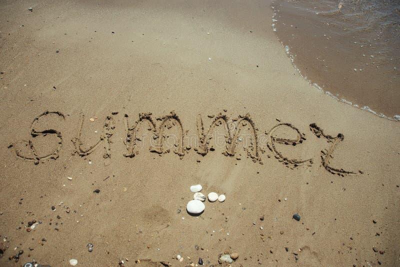 Word Summer written on sandy beach. Word Summer written on a sandy beach royalty free stock images
