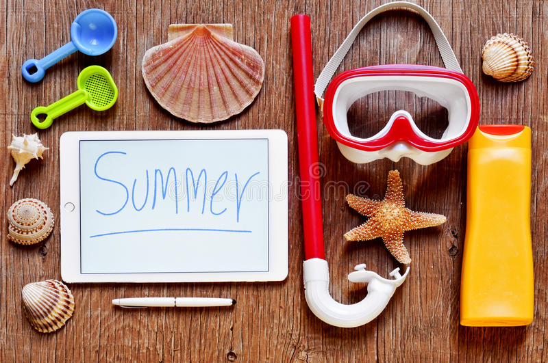 Word summer written in a tablet and summer stuff on a rustic woo royalty free stock photo