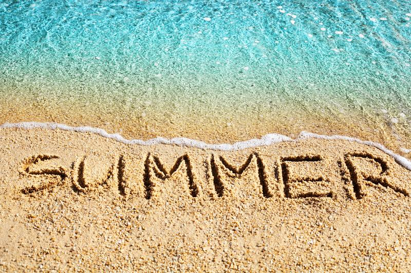 Word SUMMER written on yellow sand, blue sea water wave, white foam top view close up, handwriting letters text, summer vacations stock images