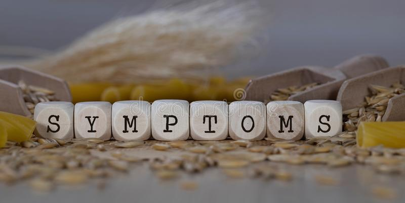 Word SYMPTOMS composed of wooden dices. Rye grains in the background. Closeup, allergen, allergy, deficiency, autoimmune, disorders, celiac, cereals, disease royalty free stock photography