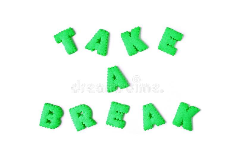 The word TAKE IT EASY spelled with lime green color alphabet shaped biscuits. On white background stock images