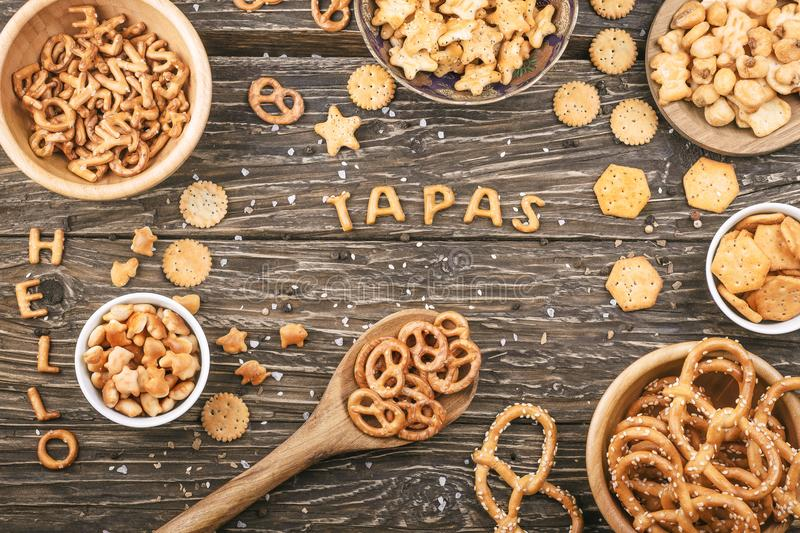 Word tapas written with crackers letters on a wooden background. royalty free stock photo
