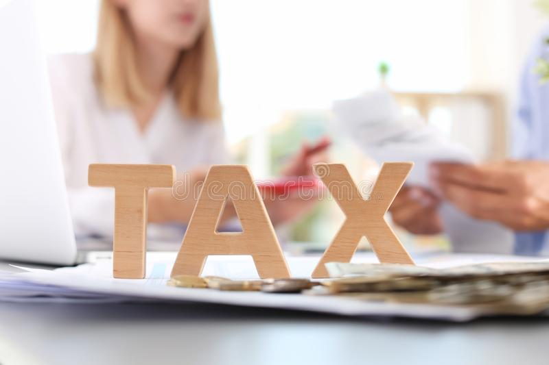 Word TAX and blurred accountants. On background stock photography
