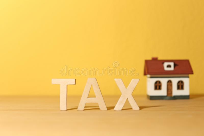 Word TAX and house model on table. Against color background stock images