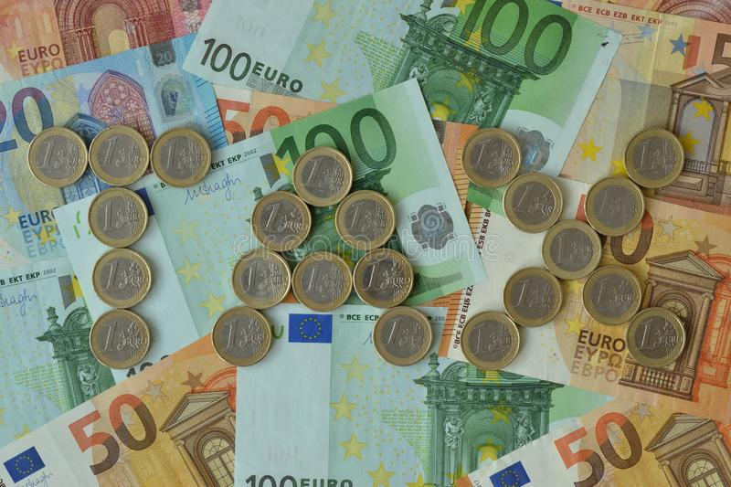 The word Tax written with euro coins on euro banknotes background royalty free stock image