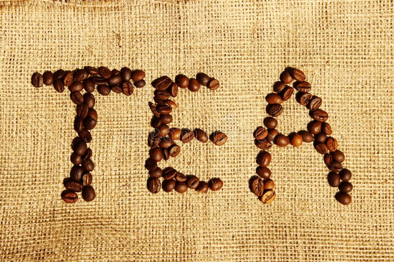 Word `Tea` Written In Coffee Beans Over Bagging Background. Coffee Beans Background. royalty free stock image