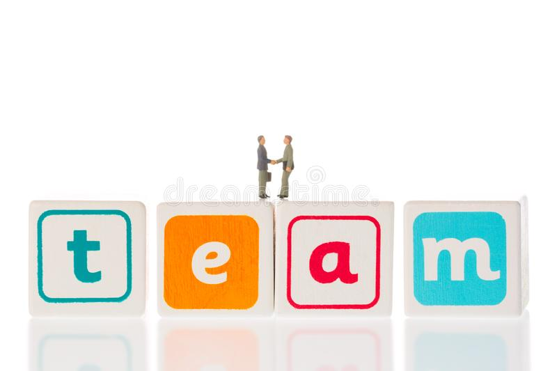 Word team made from wooden cubes with miniature businessmen handshaking isolated on white background. Teamwork concept. royalty free stock photos