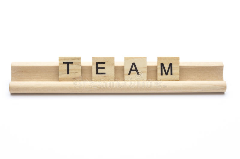Word ``team`` on scrabble wooden letters on a rack, isolated on stock photo
