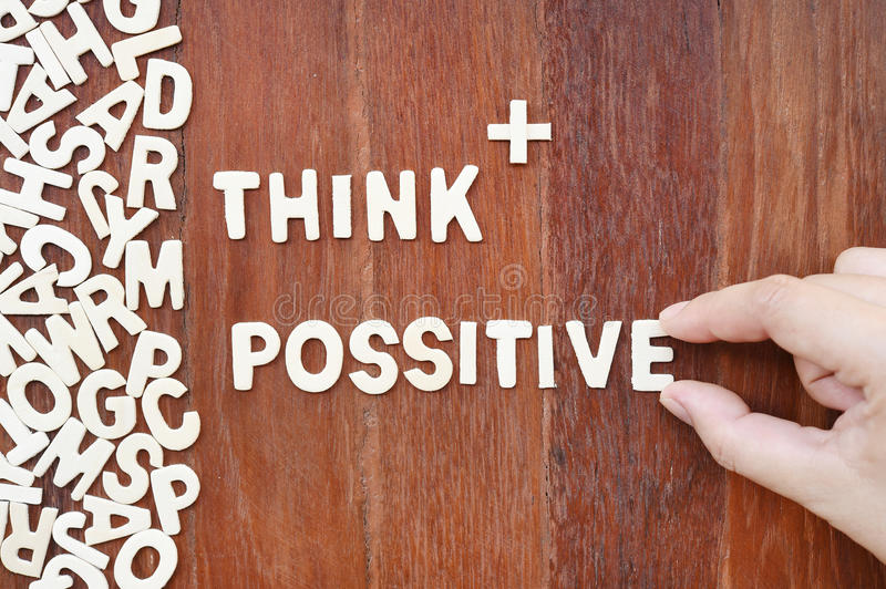 Word think possitive made with block wooden letters. Next to a pile of other letters over the wooden board surface composition stock photos