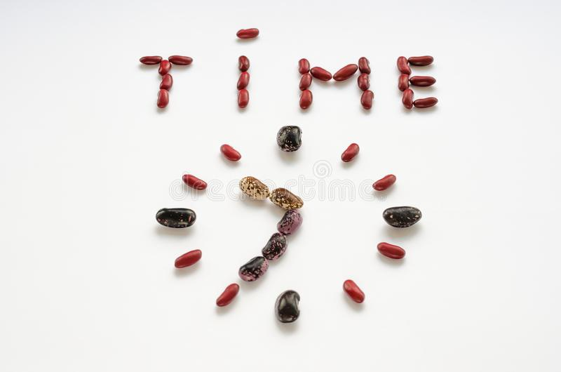 Word tijd en de wijzerplaat vormden uit kleurrijke nierbonen op witte achtergrond Gezond het Eten Concept royalty-vrije stock afbeelding