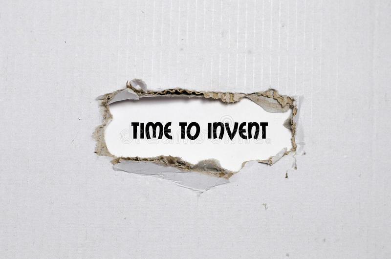The word time to invent appearing behind torn paper. The word time to invent stock photography