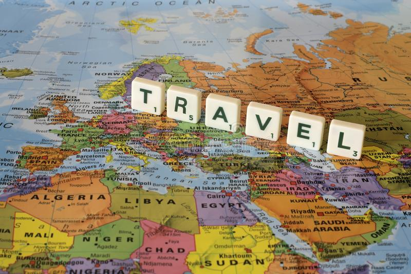 Word travel on a background colored world map. Word travel made from scrabble letter concept stock images