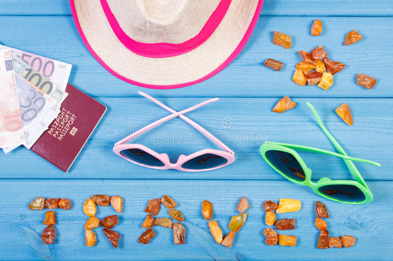 Word travel and shape of sun, sunglasses and straw hat, passport with currencies euro, summer time. Vacation time. Inscription travel and shape of sun made of royalty free stock photos