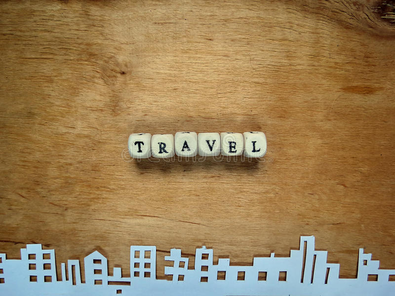 Word. Travel from the small cubes and the city cut out of paper on a wooden surface royalty free stock photo