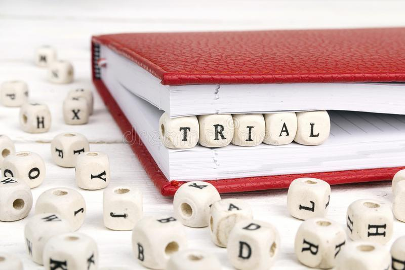 Word Trial written in wooden blocks in notebook on white wooden royalty free stock photography
