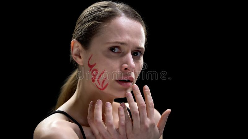 Word ugly written on lady cheek, woman feeling scared and unprotected insecurity stock photo