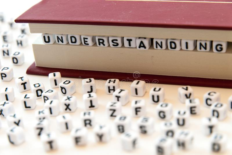 Word understanding written with letters between a book pages white background with letters spread around education reading concept. Photo stock images
