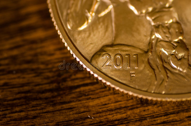 2011 (word) on United States Gold Buffalo Coin. On rosewood table royalty free stock photo