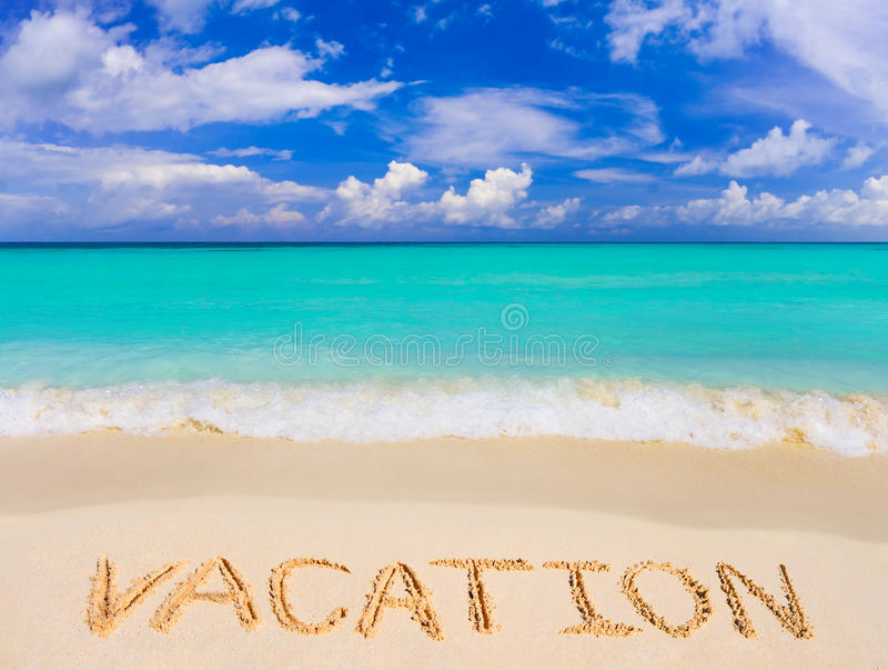 Word Vacation on beach stock photography