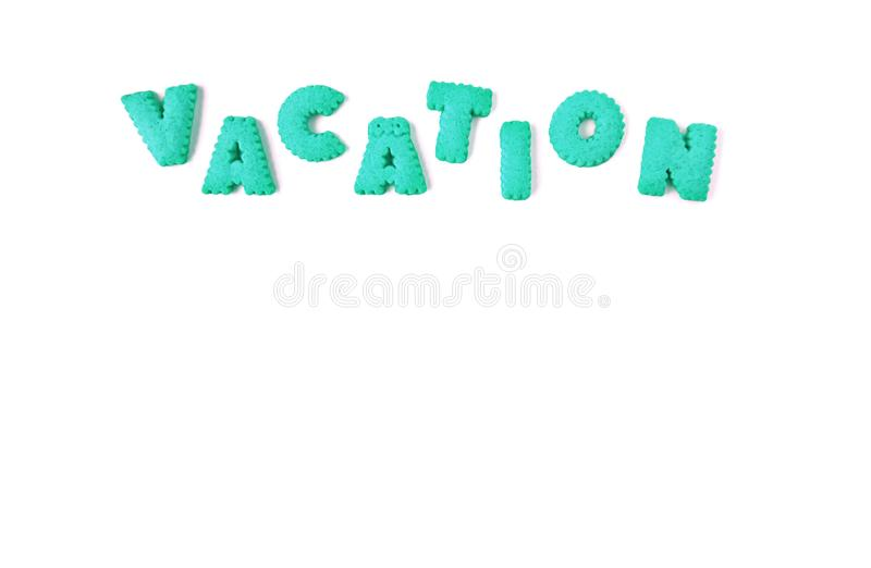 The word VACATION spelled with vibrant aqua blue color alphabet shaped cookies. On white background stock photos