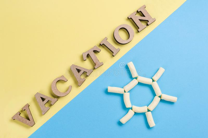 Word Vacation Wooden Letters On A Blue And Yellow Background And An