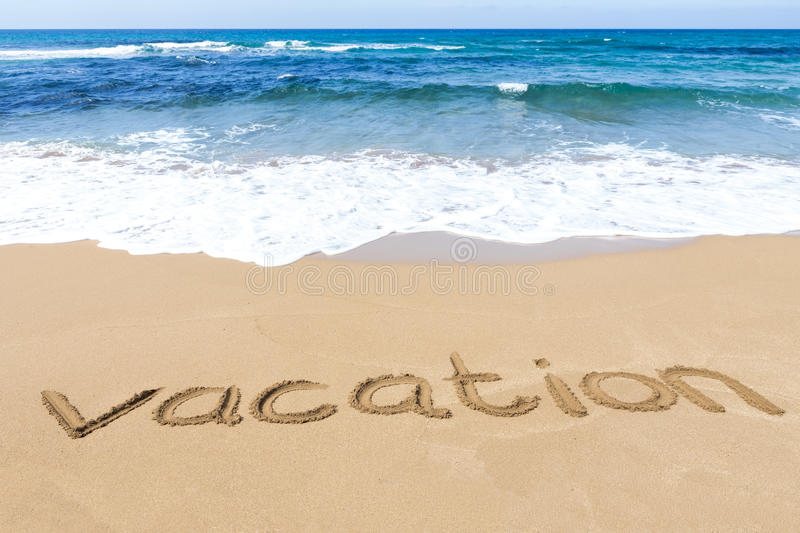 Word vacation written on sandy beach near sea stock image
