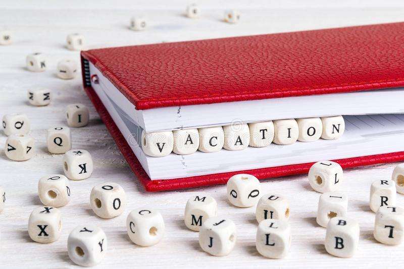 Word Vacation written in wooden blocks in red notebook on white royalty free stock image