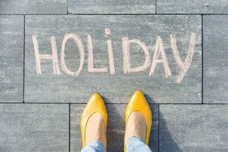 Word vakantie geschreven krijt en voeten wijfjes royalty-vrije stock afbeeldingen
