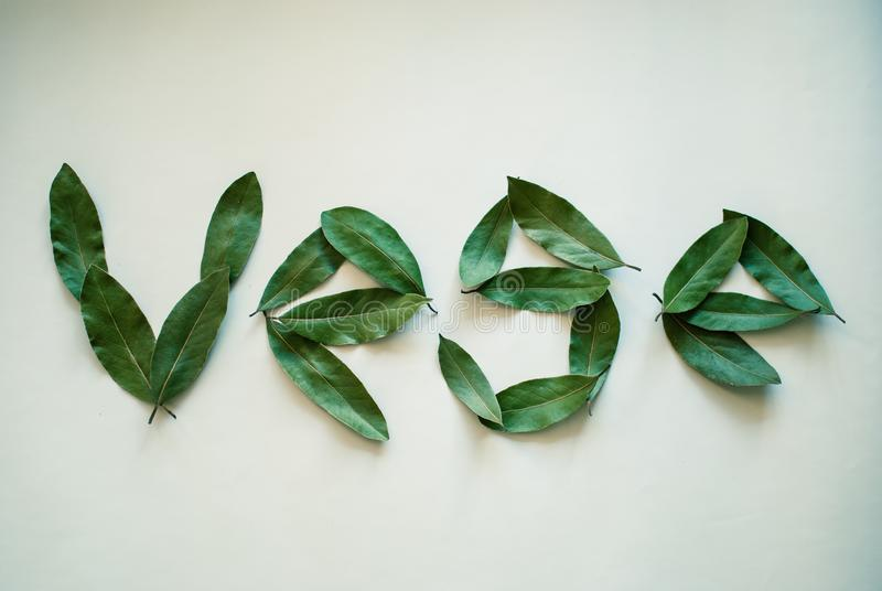 Word Vege. Bay leaves on white background. stock photo
